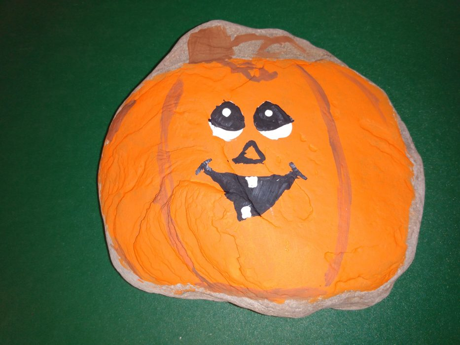 Pumpkin with cute smiling face painted on a rock. Example for the the October 2021 Paint Night